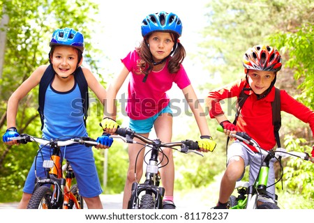 Portrait of three little cyclists riding their bikes - stock photo