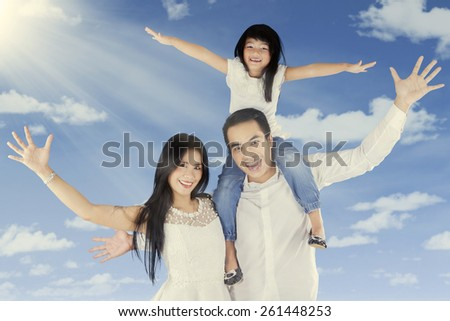 Portrait of three member of little family look happy and raise hands up under clear sky - stock photo