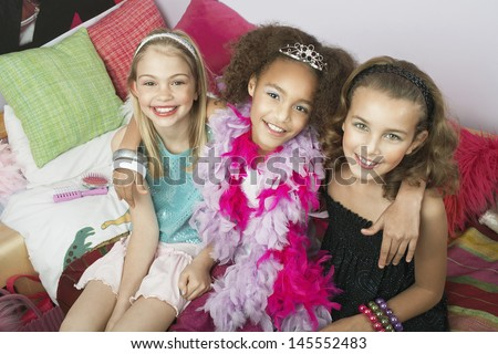 Portrait of three multiethnic girls sitting with arms around on trendy sofa at a slumber party - stock photo