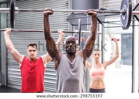 Portrait of three muscular athletes lifting barbells - stock photo