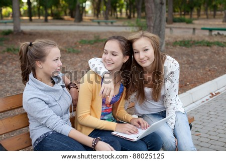 Portrait of three pretty student girls in the park surfing the internet - stock photo