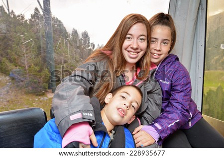 Portrait of three siblings (brother two sisters) hugging having fun in a cable car while touring the Spanish Pyrenees - stock photo