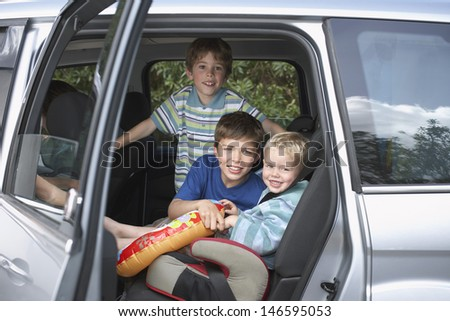 Portrait of three smiling boys in the car - stock photo