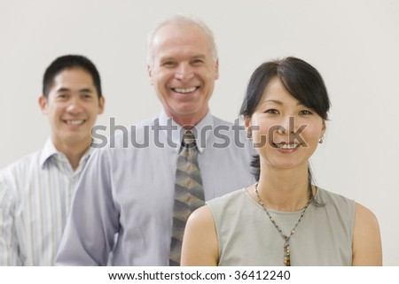 Portrait of three team members standing lined up and smiling - stock photo
