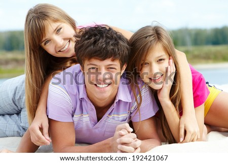 Portrait of three teenage friends looking at camera outside - stock photo
