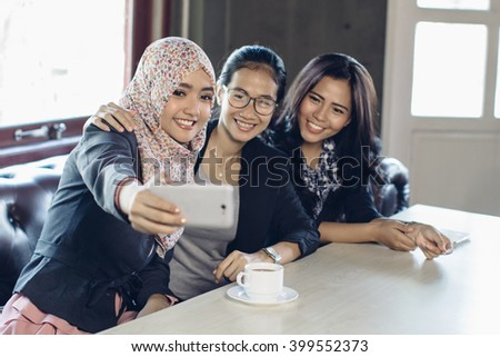 Portrait of three woman taking selfie at cafe together - stock photo
