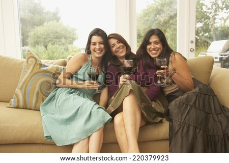 Portrait of three women sitting on couch with wine glasses - stock photo