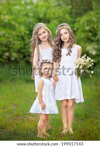 Portrait of three young girlfriends with daisies - stock photo
