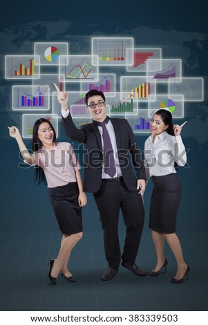 Portrait of three young multiracial businesspeople expressing their success in front financial statistics - stock photo
