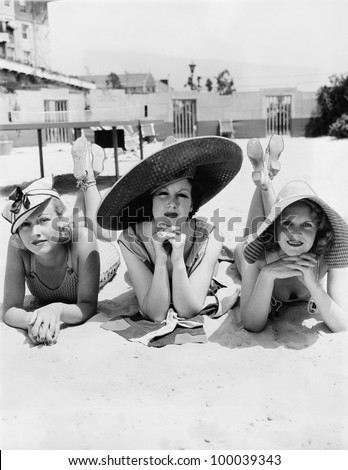 Portrait of three young women lying on the beach - stock photo