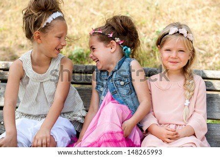 Portrait of threesome having a laugh in park. - stock photo