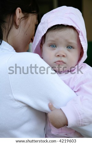 portrait of tired baby being held by mother - stock photo