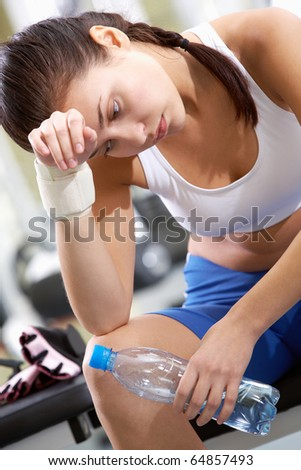 Portrait of tired brunette with bottle of water in hand having rest after workout - stock photo