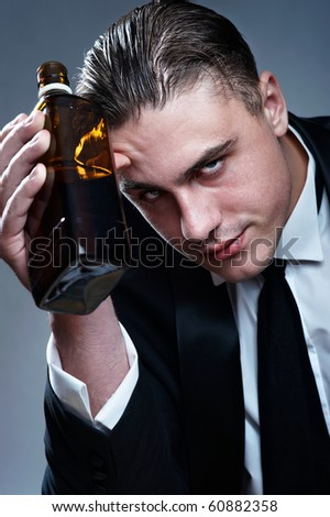 Portrait of tired drunk man with whiskey bottle - stock photo