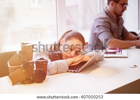 Portrait of tired freelance lady sleeping on laptop computer while many cups of coffee near by her. Pretty lady resting after hard working day. Toned picture.  - stock photo