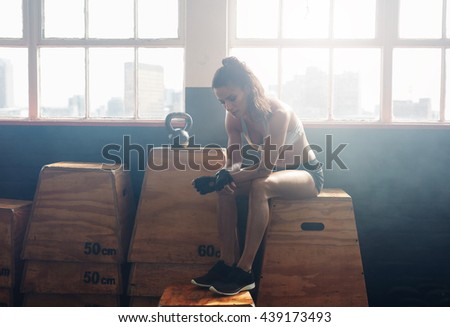 Portrait of tired looking fitness woman sitting on box at gym. She is relaxing after her intense workout. - stock photo