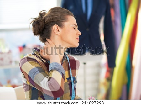 Portrait of tired tailor woman with neck pain - stock photo