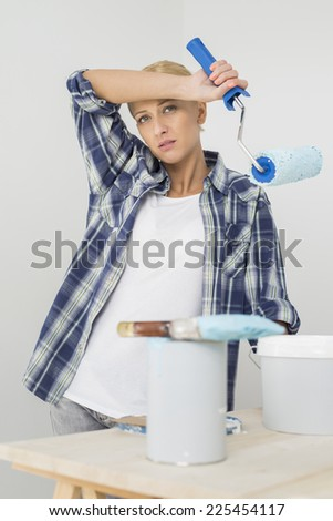 Portrait of tired woman painting new house - stock photo