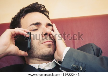 Portrait of tired young businessman making a boring conversation on cellphone on sofa. - stock photo