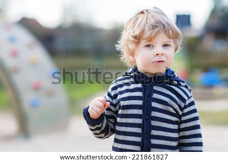 Portrait of toddler boy having fun on outdoor playground. - stock photo