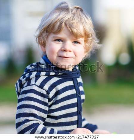 Portrait of toddler boy having fun on outdoor playground. Spring sunny day. Square size. - stock photo
