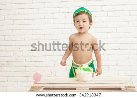 portrait of toddler wearing green hat and pants with his sponge cake on white walls background - stock photo