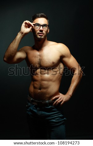 portrait of topless athletic macho man in glasses posing over black background - stock photo