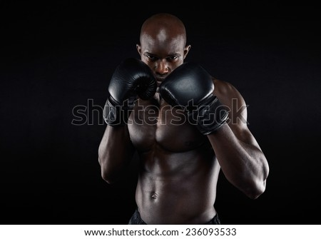 Portrait of tough male boxer posing in boxing stance against black background. Professional fighter ready for boxing match. - stock photo