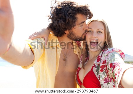 Portrait of tourist couple using technology to take selfies pictures of themselves pulling faces, enjoying a summer holiday together on a beach on vacation, outdoors. Travel and technology lifestyle. - stock photo