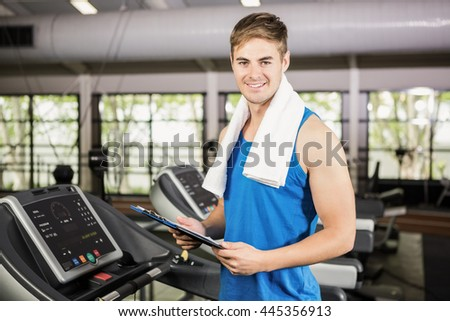 Portrait of trainer holding clipboard on treadmill at gym - stock photo