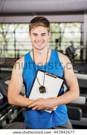 Portrait of trainer standing in gym with clipboard and stopwatch - stock photo