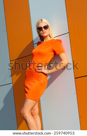 Portrait of trendy fashion girl in sunglasses and in orange dress on the background  of orange wall - stock photo