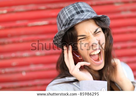 Portrait of trendy girl shouting on the phone - stock photo