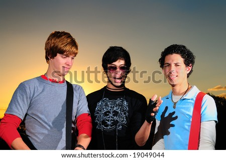 Portrait of trendy young friends posing against sunset background - stock photo