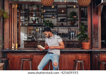 Portrait of trendy young man sitting at a cafe counter reading a book and drinking coffee - stock photo