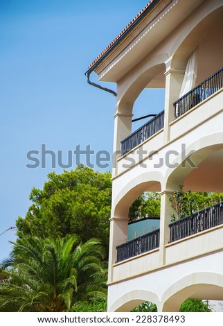 Portrait of tropical apartment building with palms. - stock photo