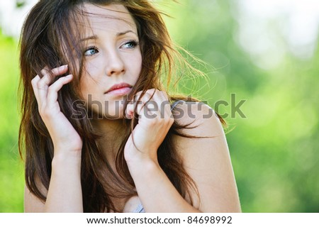 Portrait of troubled beautiful brunette girl looking somewhere at summer green park. - stock photo
