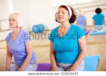 Portrait of two aged females doing exercise for relaxation in sport gym  - stock photo