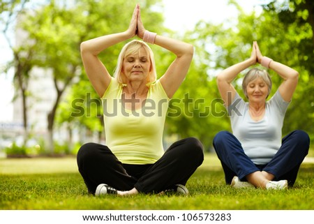 Portrait of two aged females doing yoga exercise in park - stock photo