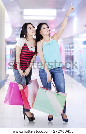 Portrait of two asian woman with shopping bags standing in the mall and looking at copyspace - stock photo