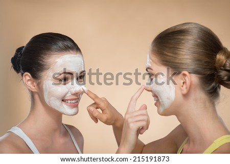 Portrait of two beautiful girls with cream on their  faces looking on each other  and touching their noses and laughing  isolated on beige background with copy placer - stock photo