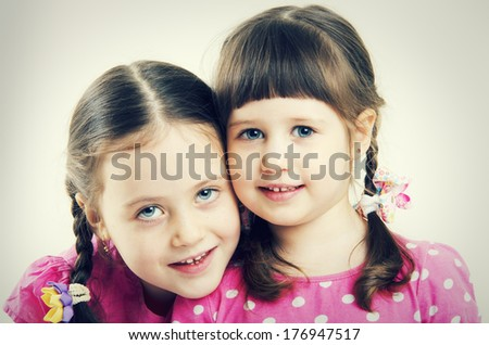 Portrait of two beautiful happy little sisters - stock photo