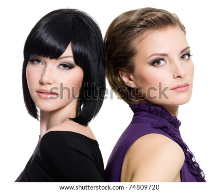 Portrait of  two beautiful sexy girlfriends standing together on white background - stock photo