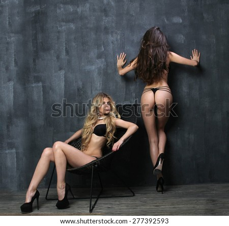 Portrait of two beautiful women in erotic lingerie, photo in front of blue studio background - stock photo