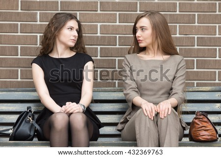 Portrait of two beautiful young female rivals sitting side by side on bench and looking at each other with challenging expressions. Attractive caucasian office women ready for confrontation - stock photo