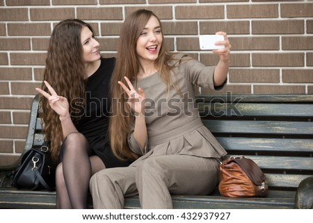 Portrait of two beautiful young girlfriends sitting on bench and taking a selfie on the street. 2 Happy attractive women friends making self-portrait with smartphone - stock photo