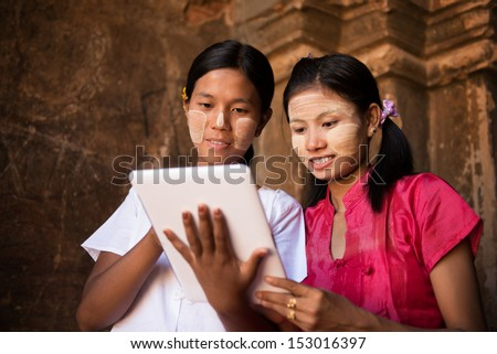 Portrait of two beautiful young traditional Myanmar girl using digital tablet pc together. - stock photo