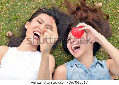 Portrait of Two Beautiful , Young Women , Lie Down on Lawn - stock photo