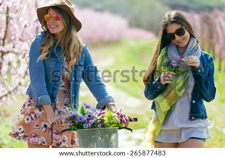 Portrait of two beautiful young women with a vintage bike in the field. - stock photo