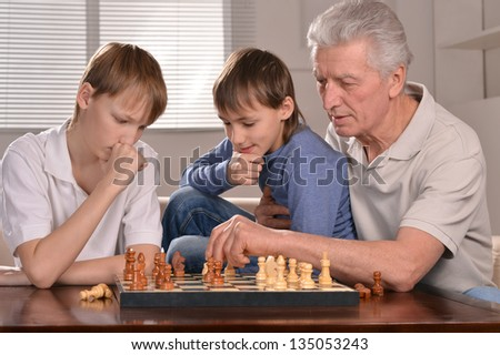 Portrait of two boys and grandfather playing chess at home - stock photo